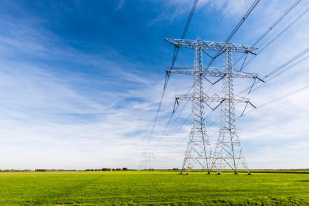 torres de alta tension: Líneas de alta tensión y torres de energía en un paisaje agrícola plana y verde en un día soleado con nubes cirros en el cielo azul.