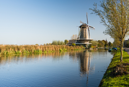 Dutch polder landscape with a windmill and a canal  on a sunny day in the autumn season. photo