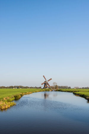 polder: Stream with a mirror smooth water surface in a rural Dutch polder landscape and in the background an historic windmill with brown sails.