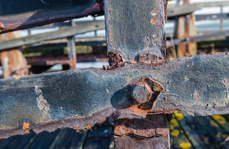 Part of a neglected wooden jetty with rusted iron beams and bolts from close. photo
