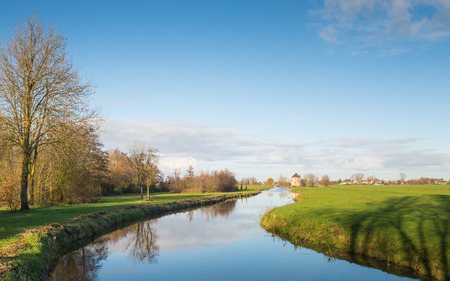 Polder landscape in the Netherlands with a small meandering river on a sunny day in the fall season. photo