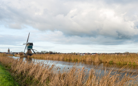 Post mill along a small river with yellowed reed in the Netherlands on a cloudy day in the fall season. photo