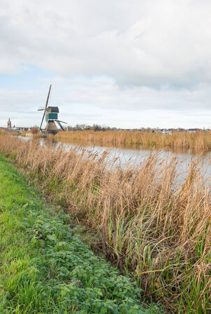 Hollow post mill in the Netherlands beside a small river with yellowed reedfs on a cloudy day in the autumn season. photo