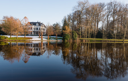 windless: Dutch 19th century manor house with a high slate roof at a river with a reflecting mirror smooth water surface on a sunny and windless winter day.