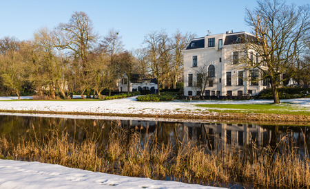 windless: Dutch 20th century manor house from 1909 at a river with a reflecting mirror smooth water surface on a sunny and windless winter day.