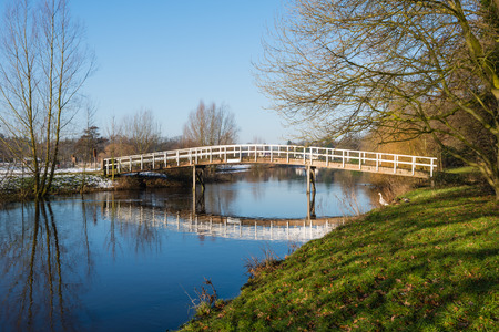 Wooden bridge with a white railing reflected in the mirror smooth water surface of a small river on a sunny day in the winter season. photo