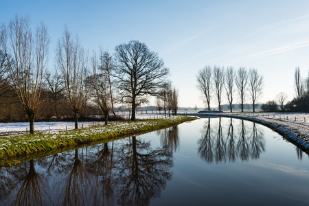 Different kinds of bare trees reflected in the mirror like water surface of a small river with snow on the banks. photo