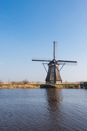 Dutch windmill next to a canal on a sunny day in springtime. photo