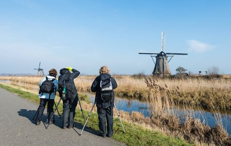 Three unknown tourists are photographing the famous Dutch windmills in Kinderdijk on a sunny day in springtime. photo
