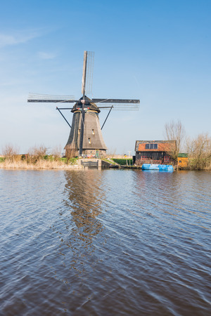 Dutch windmill and a small barn next to a canal on a sunny day in springtime. photo