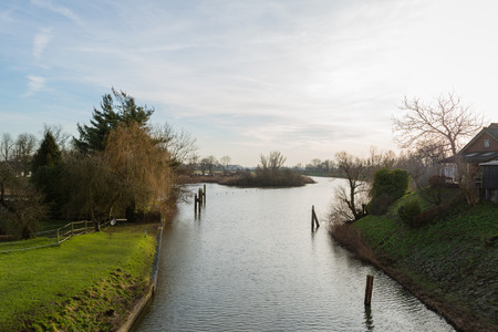 View at a small Dutch river at dusk on a quiet  day in the winter season. photo