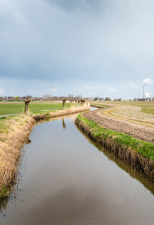 meanders: A narrow ditch winds through the landscape. It is a gray cloudy day at the end of the winter. Stock Photo