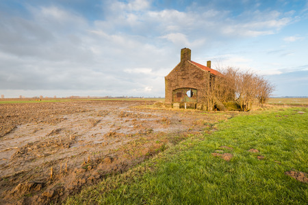 Abandoned and neglected small building in a wet clay field with corn stubble. photo