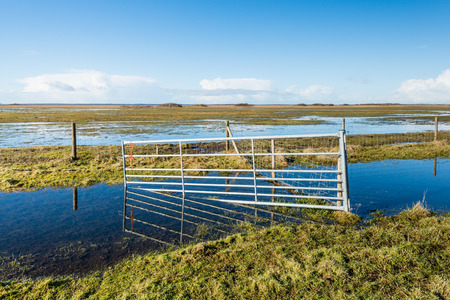 Flooded nature reserve and a crooked steel gate reflected in the mirror smooth water and ice surface on a clear and sunny day in winter. photo