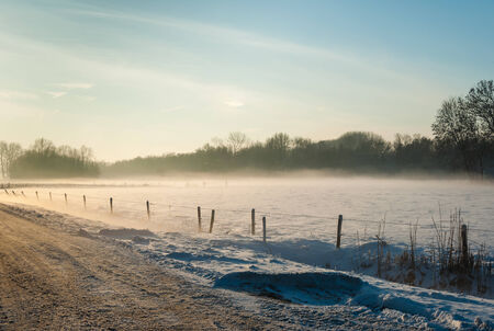 Snowy country landscape in low afternoon sunlight on a foggy day in the winter season. photo