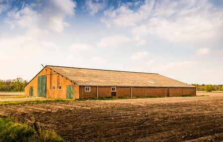 barn doors: Old brick barn with a corrugated roof and green painted wooden doors. In the foreground a field with the ridges of newly sown potatoes.