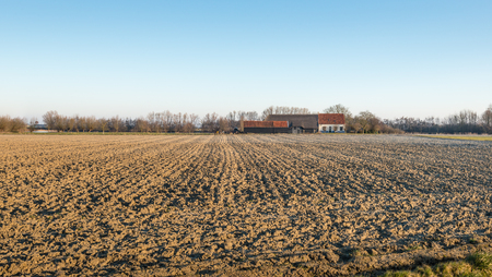 A ploughed field in the foreground and in the background an old farm with a barn. It photo
