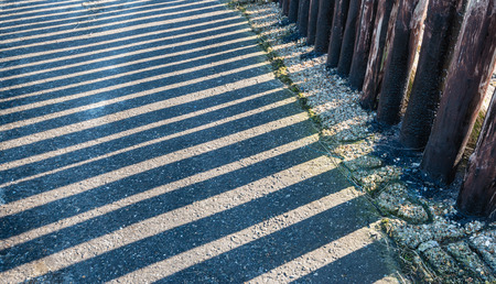 groyne: Parallel shadows of a row of wooden posts on a concrete groyne in a Dutch estuary. Stock Photo