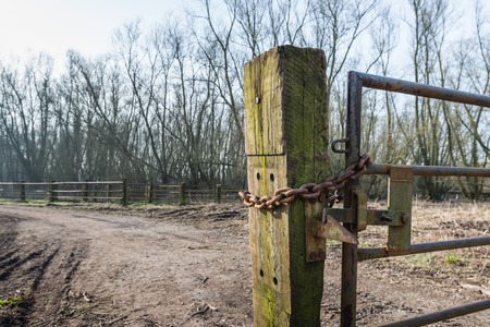 crooked: Part of a crooked old gate mounted on an oak railway sleeper. The rusty iron gate is closed and locked with a chain and a padlock.