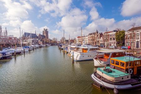 Cityscape van de oude stad Dordrecht motorjachten afgemeerd aan meerpalen in het kanaal en de historische kerk van Onze-Lieve-Vrouw in de achtergrond.