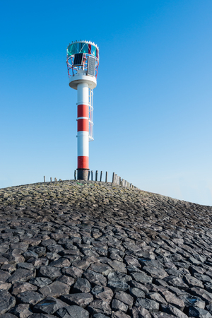 navigational light: Red and white visual beacon at the end of a pier built of basalt blocks. On the pier are wooden posts against the waves.