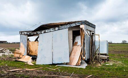 Site kantoor in het veld vernietigd door de zware storm. Donkere dreigende wolken opdoemen in de lucht.