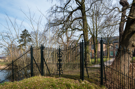 Green painted wrought iron fence with a locked gate in front of an historic country house in the Netherlands.