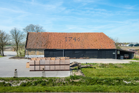 Old Dutch farmers barn built in 1746. The historic building has an orange colored tiled roof. photo