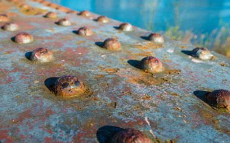 rusting: Closeup of a section of a historic railroad bridge with large rusting rivets on a sunny day. Stock Photo