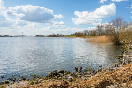 ashore: Banks of a wide Dutch river at the beginning of spring. There is a lot of debris washed ashore. Stock Photo
