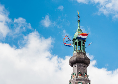 breda: Close-up of the 97 meter high spire of the Grote Kerk or Onze LIeve Vrouwe Kerk at the Grote Markt in Breda Centre with waving tricolor flags and orange pennants for the yearly celebration of Kings day.