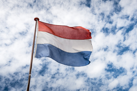 Flag of the Kingdom of the Netherlands in red, white and blue strips of fabric fastened at a flagpole or a ship and blowing in the wind. photo