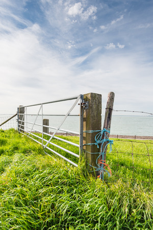 meshed: Galvanized gate between two wooden beams and a fence with coarse meshed netting and barbed wire attached with different colored ropes. Stock Photo