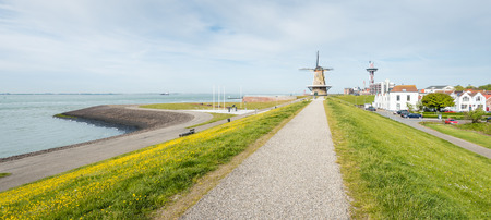flour mill: Cityscape of the Dutch city of Vlissingen from the seawall. The mill (Oranjemolen) at the end of the path is a flour mill built in 1691 or earlier and restored restored. Stock Photo