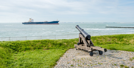 movable: Movable historic cannon on the bank of the Dutch city of Vlissingen ostensibly focused on a accidentally passing freighter. Stock Photo