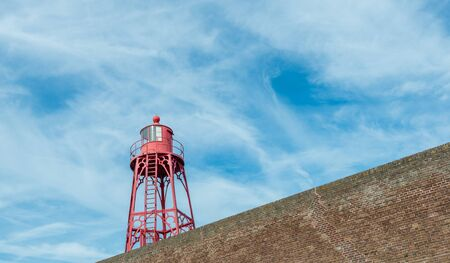next year: Red metal lighthouse next to a masonry wall at the North Sea coast in the Netherlands. The tower was constructed in the year 1891. Stock Photo