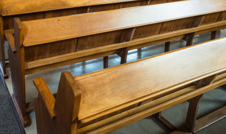 Rows of wooden church benches without anybody from close.
