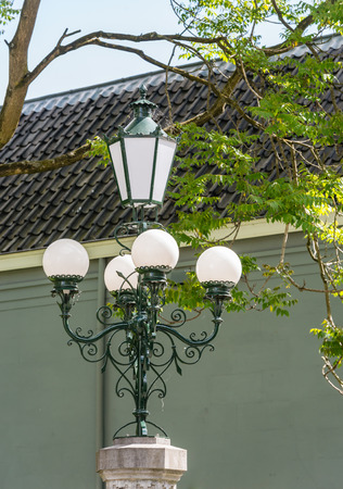 Restored historic lighting from 1896 at the entrance to an old park in the Netherlands. The original gas lighting was later converted into an electric. More recently, LED bulbs were attached in the fixtures.