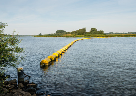 switched: Wide creek in a Dutch nature reserve closed with a barrier of floating switched yellow plastic objects