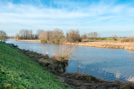 windless: Dutch rural landscape on an almost windless day in the winter season with a narrow river meandering between the banks.