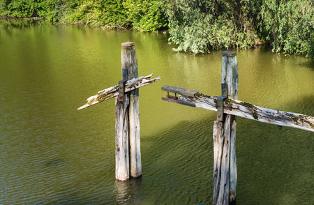 mooring bollards: Bollards and other components of a neglected old wooden jetty in a small river in a nature reserve.