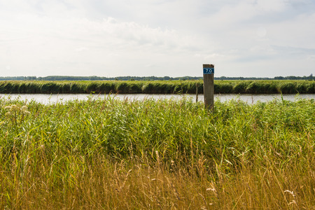 numeral: Narrow river in a flat Dutch landscape in the summer season. On the shore is a wooden hectometre pole with a blue sign with the numeral 7.0.