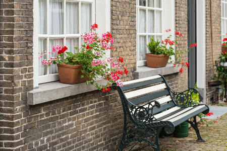 iron curtain: White painted window with lace curtain in a masonry wall. On the stone windowsill are pink and red flowering pelargonium plants in pots. The green bench in front of the facade is made from wrought iron and wood.