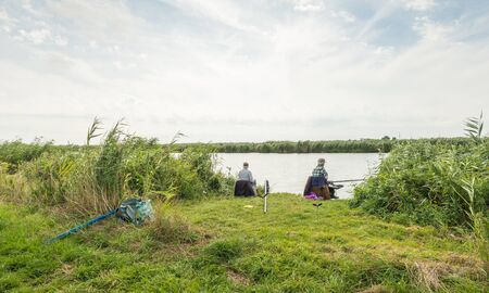 quietly: Two older anglers fishing quietly sitting among the reeds on the bank of a river.