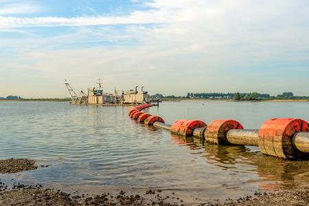 Draga de succión en un río holandés chupa la arena y la grava del fondo del río y lo transporta a través de una tubería flotante con flotadores naranjas a la orilla. Foto de archivo