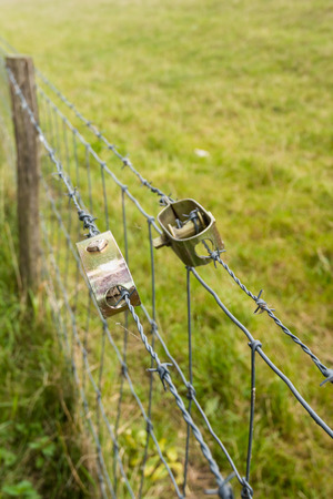 sheeny: Two new wire stretchers tensioning the barbed wire of the fence around the grass on the slope of the dike. Stock Photo