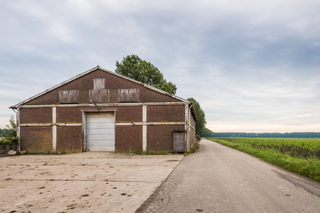 sectional door: Big agricultural old barn with a large entrance situated along a country road in a rural area on a cloudy summer day.