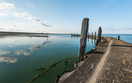 windless: Weathered concrete breakwater with a rusty sheet pile and angled wooden beams reflected in the mirror smooth water surface on a windless day with a blue sky.