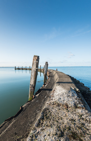 bollards: Weathered concrete breakwater with a rusty sheet pile and angled wooden beams in the mirror smooth water surface on a windless day with a blue sky.