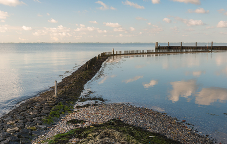 windless: Pier of basalt blocks and wooden beams reflected in the mirror smooth water surface on a windless day with a blue sky and some clouds.